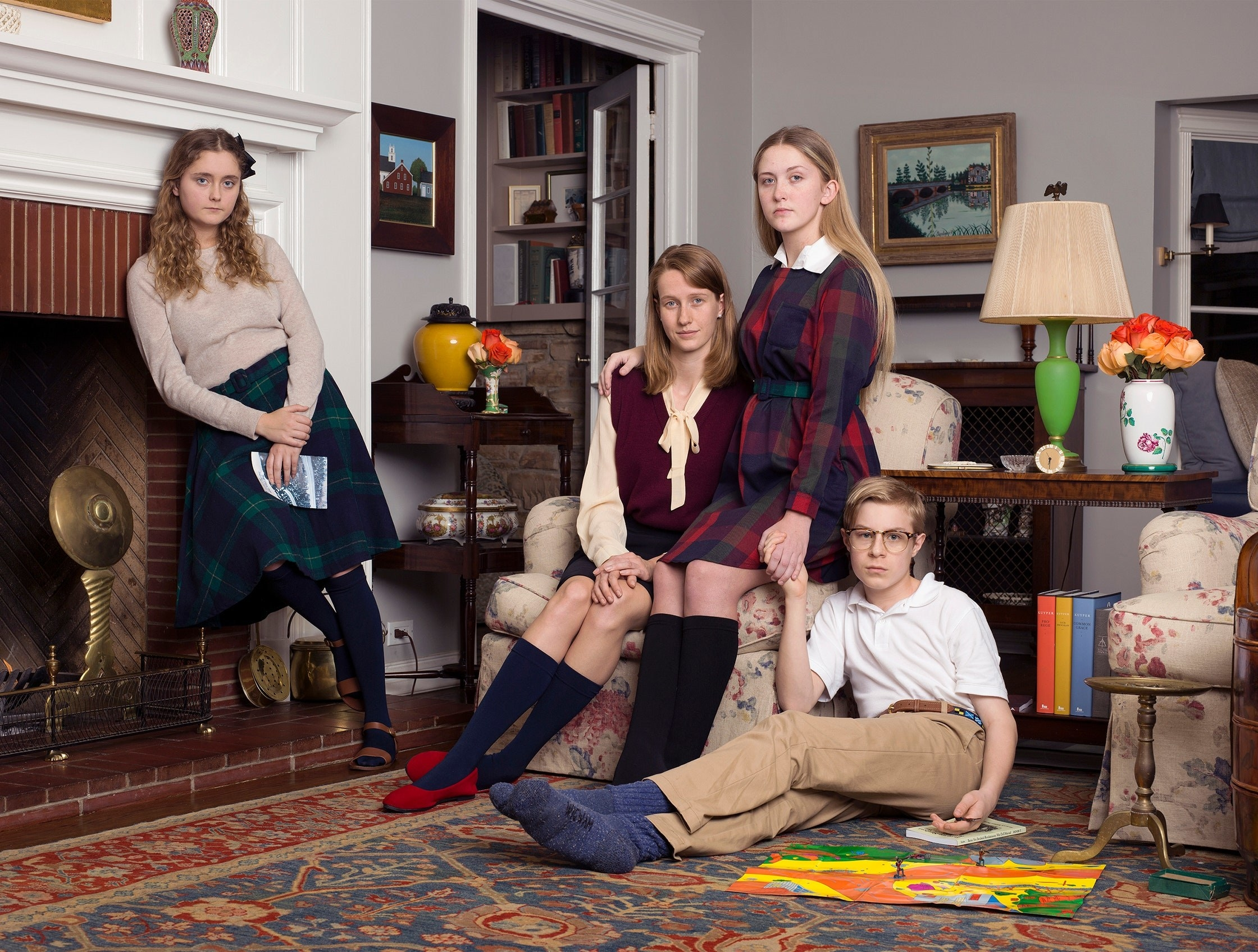 A group of conservatively dressed children sit or stand in room with a rug, fireplace, paintings, and bookshelves