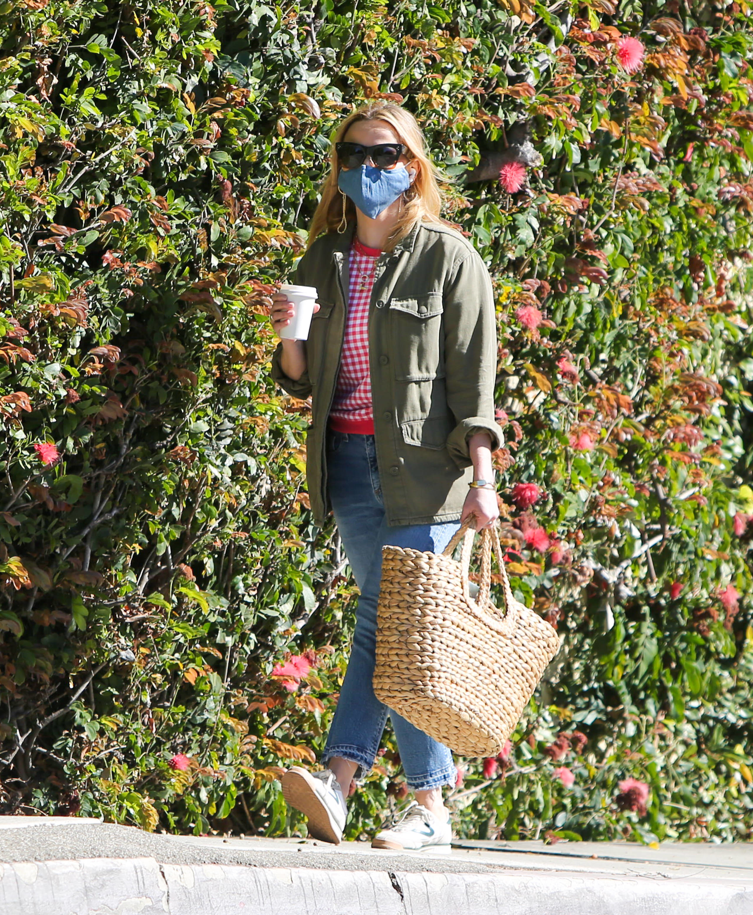 Reese wears a patterned sweater underneath a cargo jacket. She's also wearing a face mask, sneakers, sunglasses, straight leg jeans, and holding a giant woven basket purse.