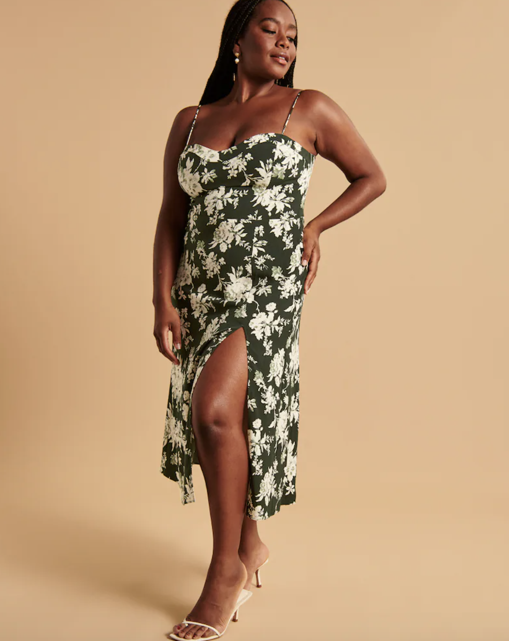 model wearing the mid-length spaghetti-strap dress in green with white flowers all over it