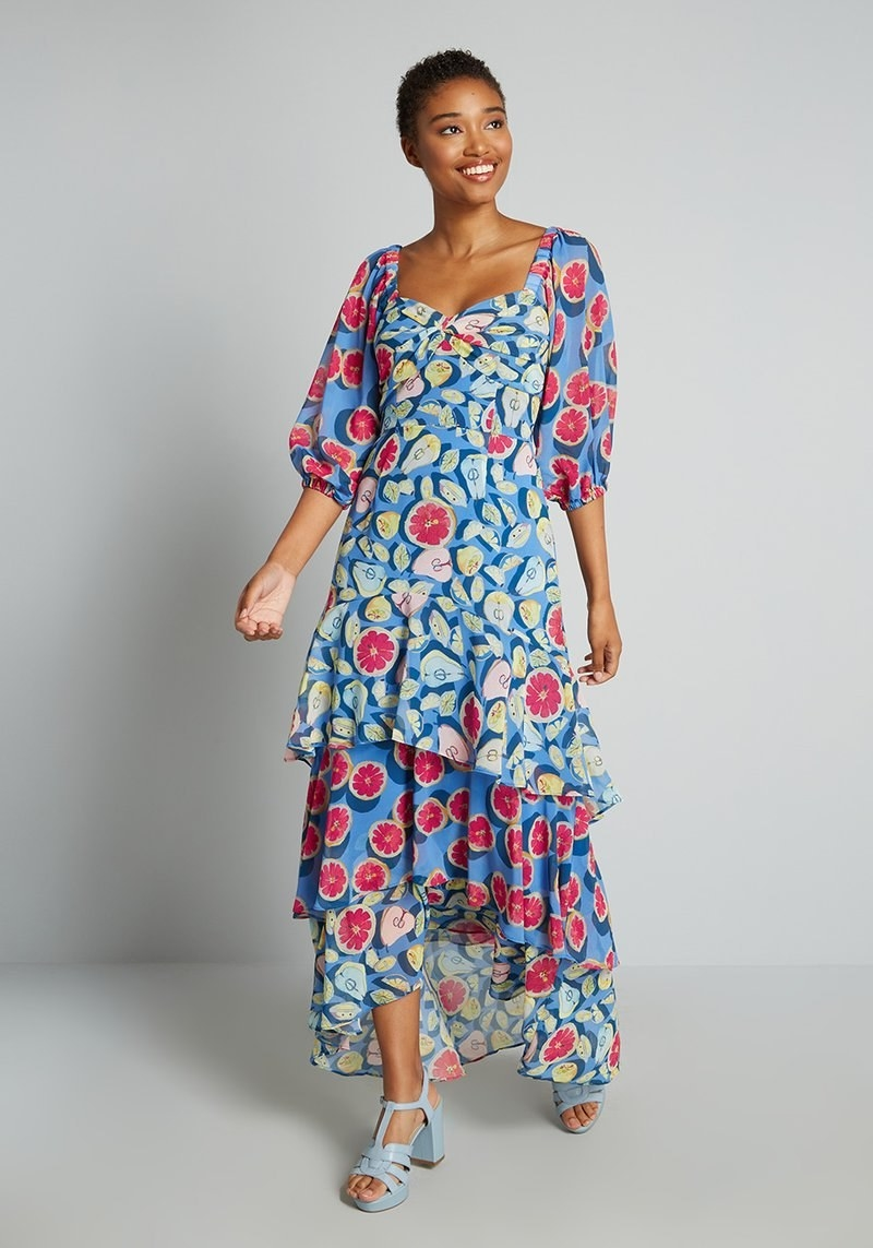 model wearing the multi-colored blue tiered maxi dress with illustrations of pears and grapefruits all over it