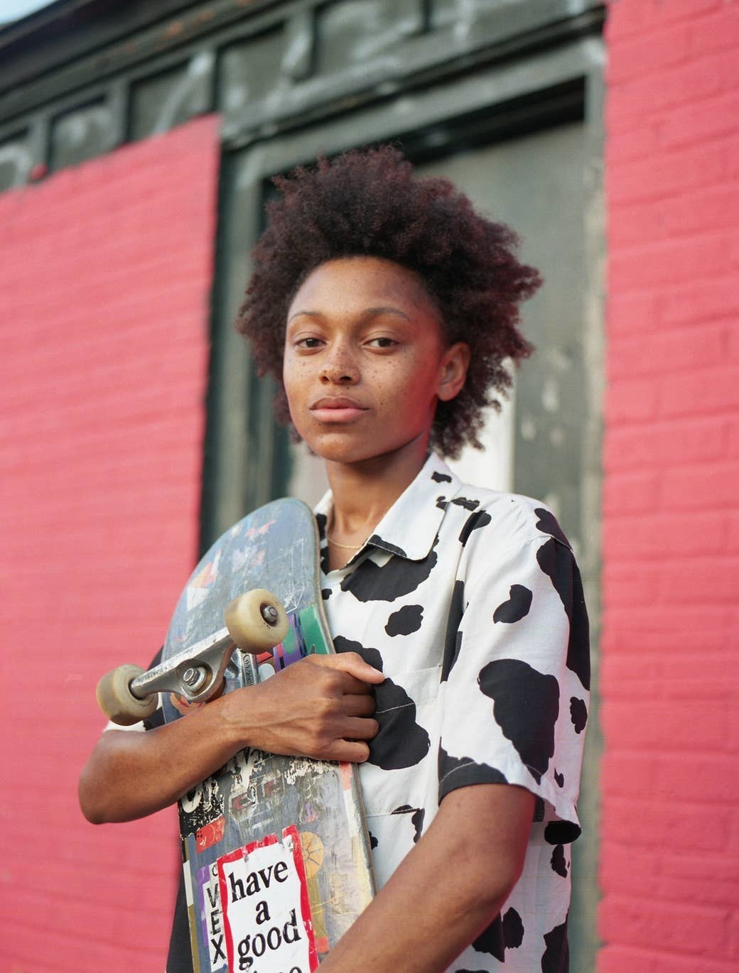 A young girl in a cow-print shirt holding a skateboard in front of a painted brick wall