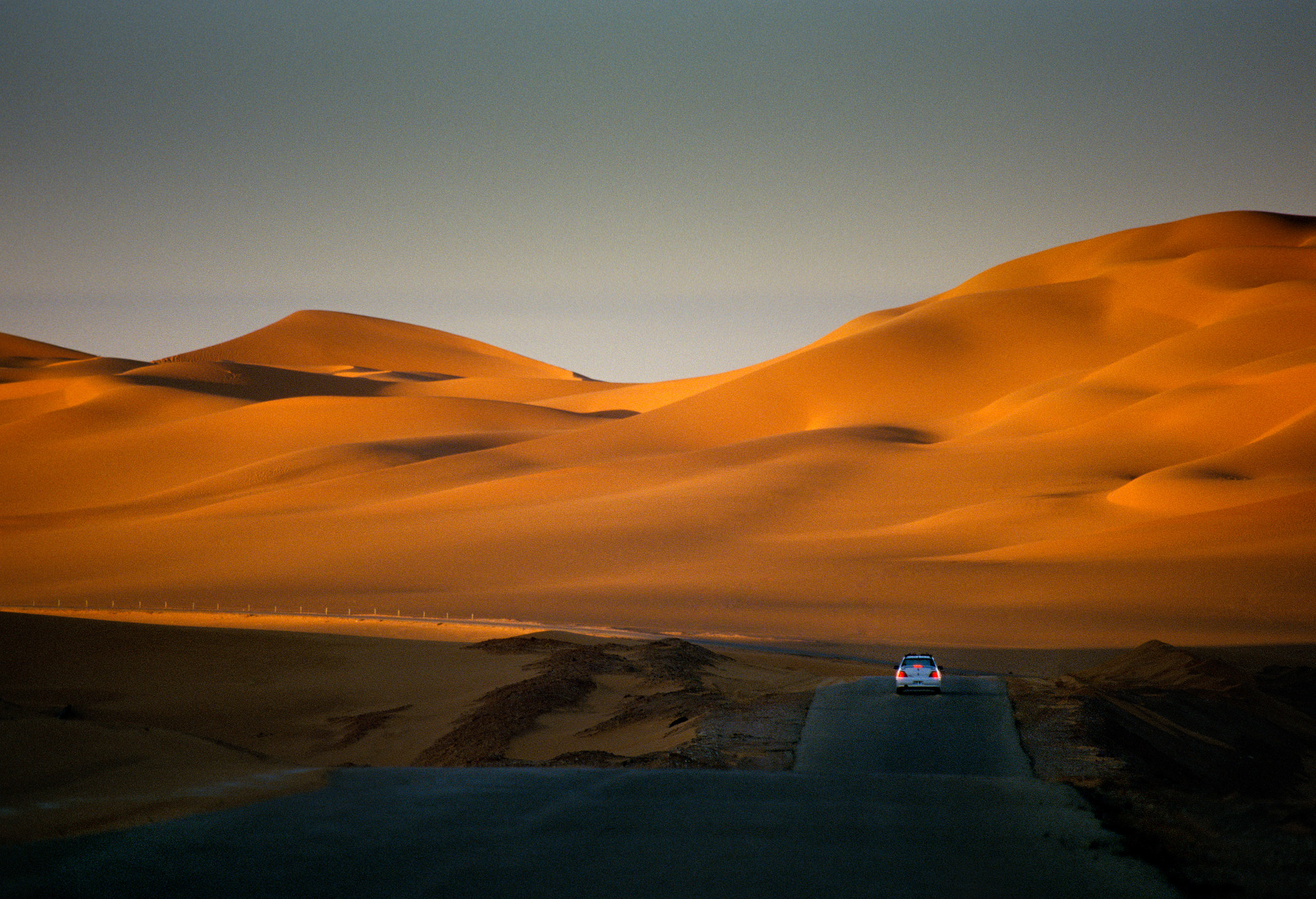 A road leading to the Sahara desert sand dunes.