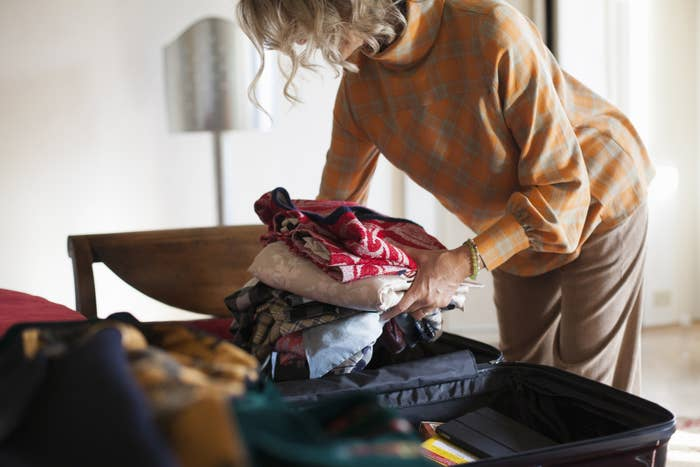 A woman packing a suitcase.
