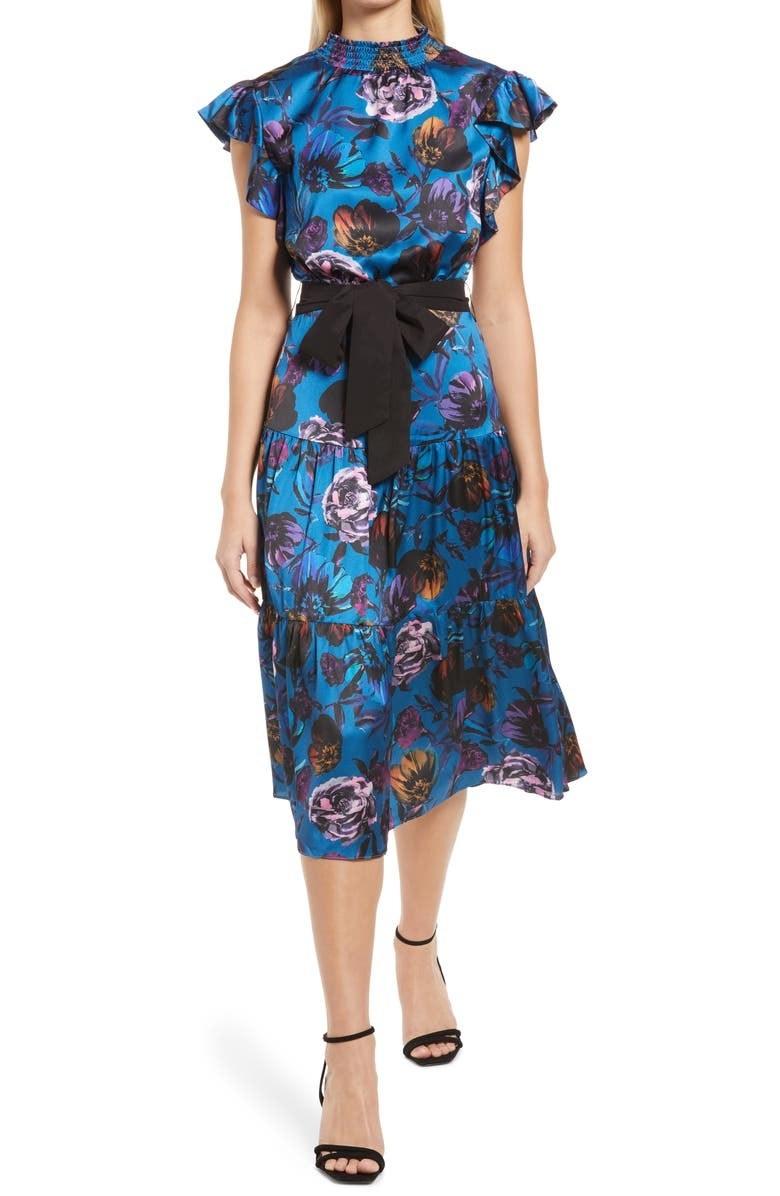 model wearing the mid-length high-neck dress in blue with black, orange, and pink flowers all over it