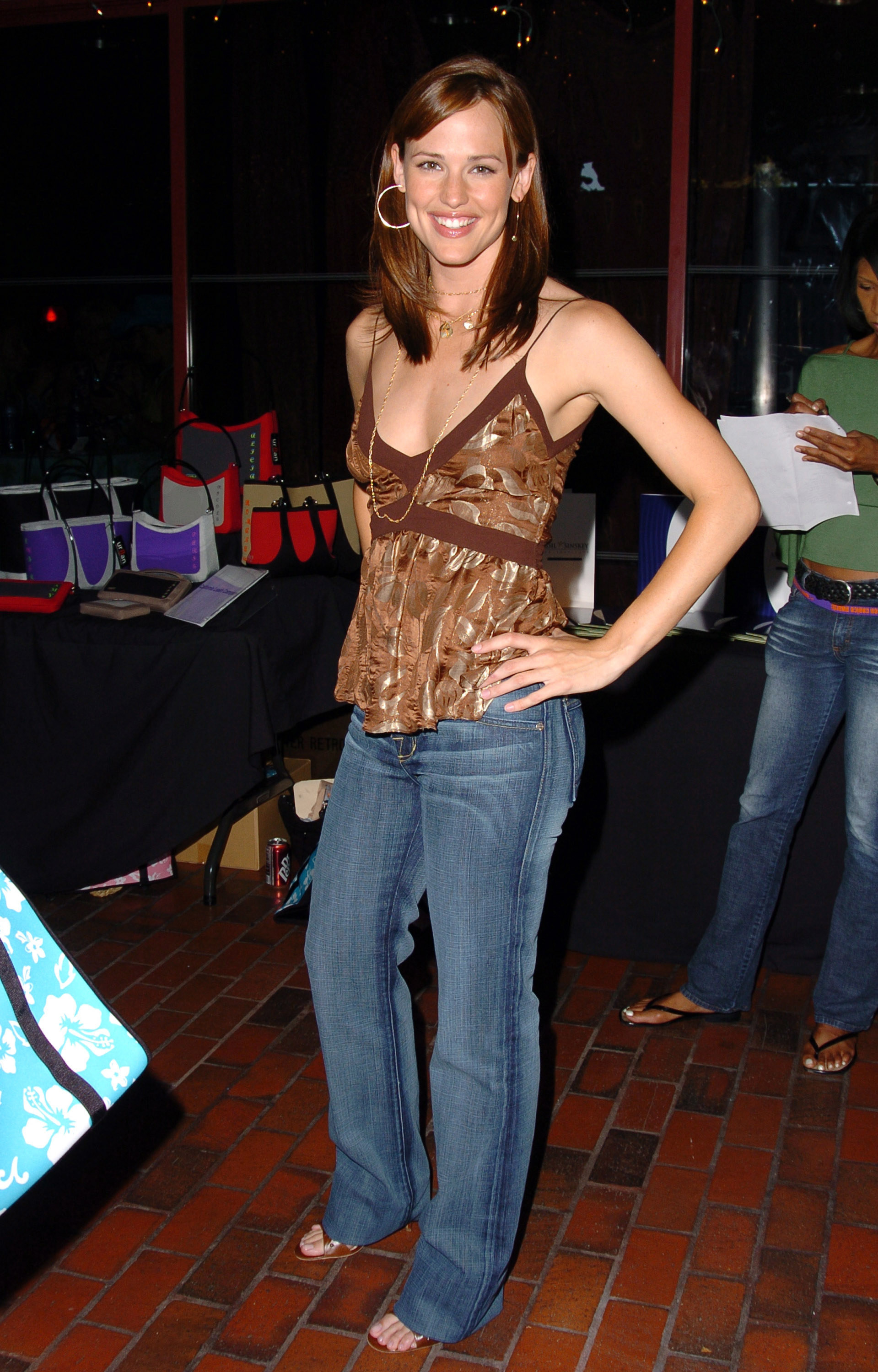 Jennifer wears a shimmery camisole with jeans, hoop earrings, and sandals.