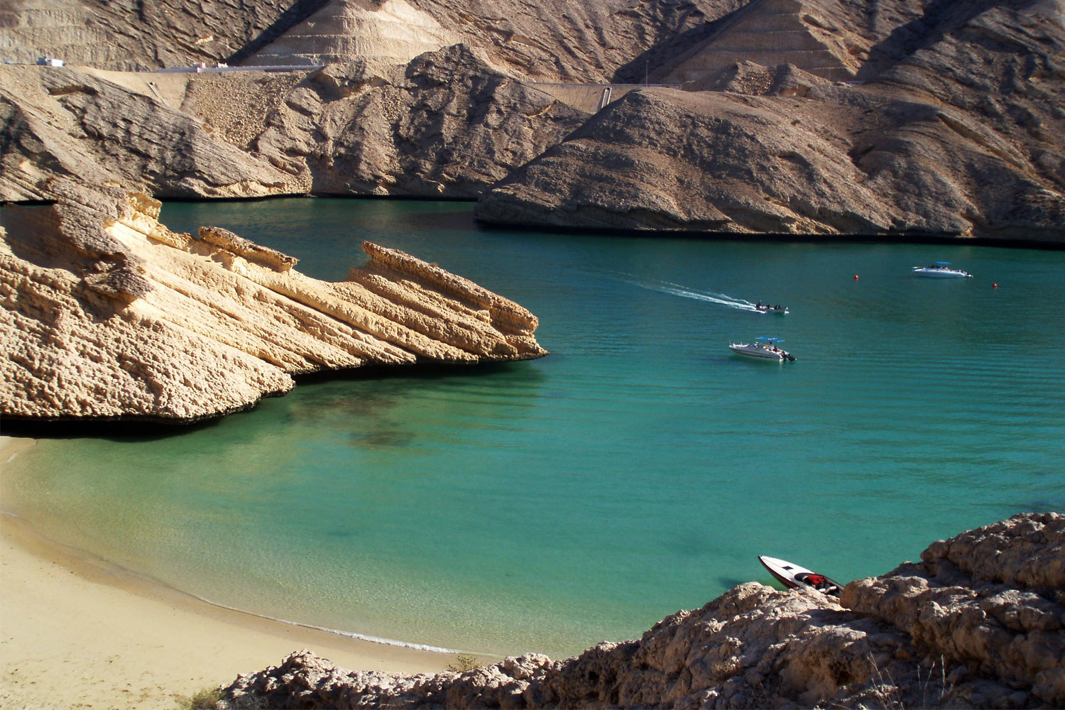A beach surrounded by rocky cliffs in Oman.