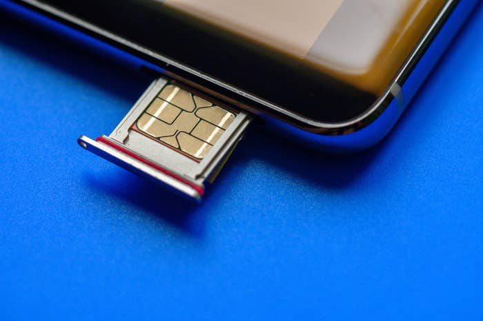 A SIM card being inserted into a phone.