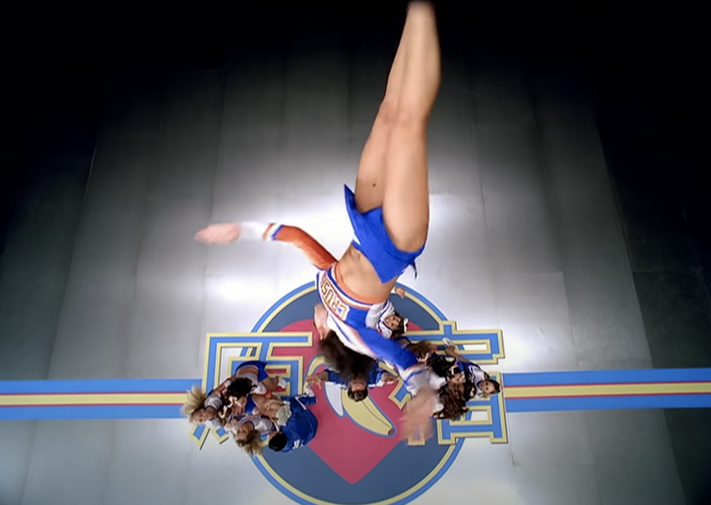 A camera angle from directly above a group of cheerleaders as one of them flips into the air toward the camera