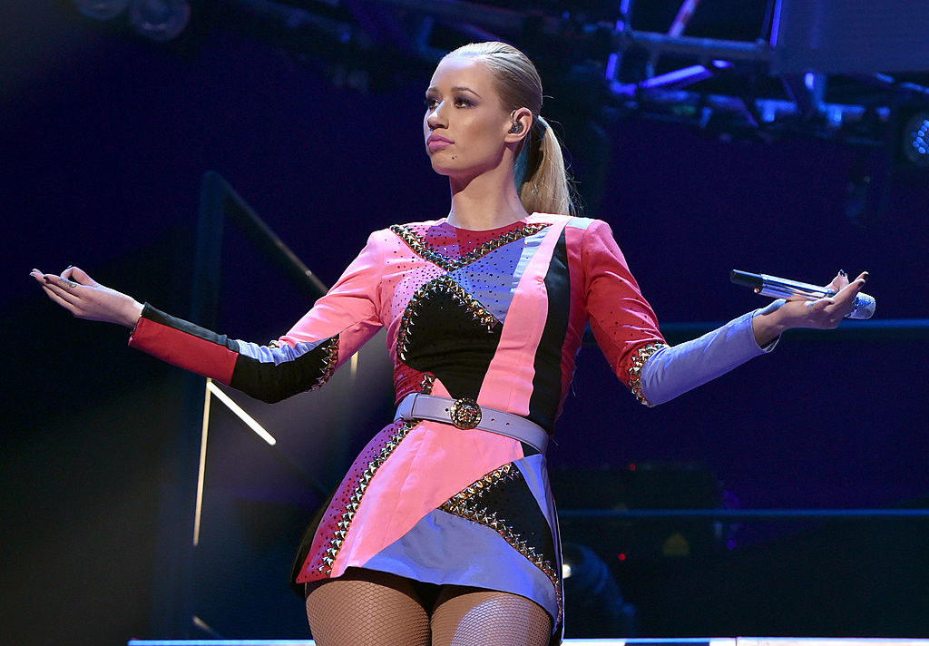 Iggy holding her arms out to the crowd as she performs on stage