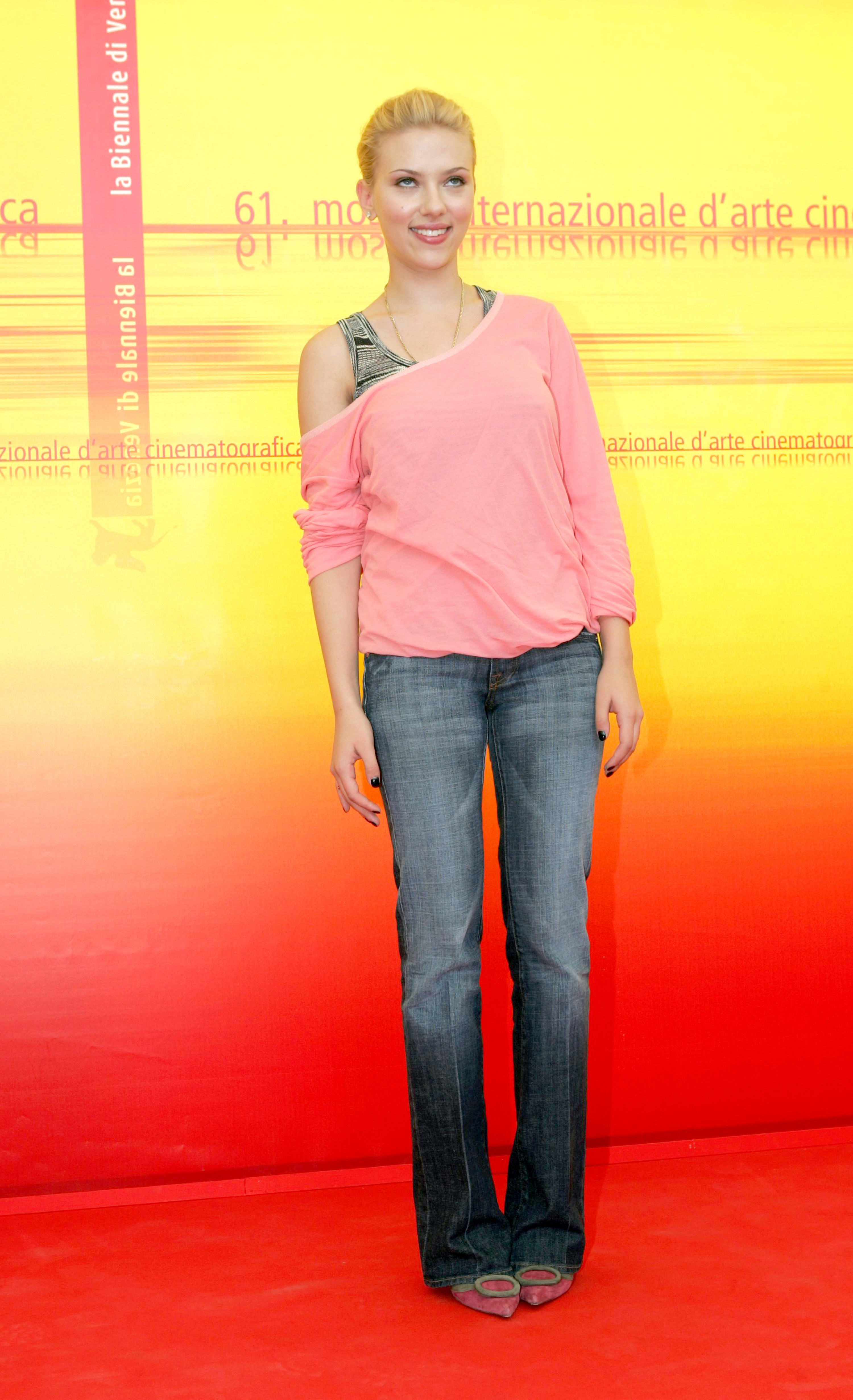 Scarlett wears a pink off the shoulder t-shirt with a striped tank top underneath. She also wears bootcut jeans and pointy-toed heels with giant circles on them.