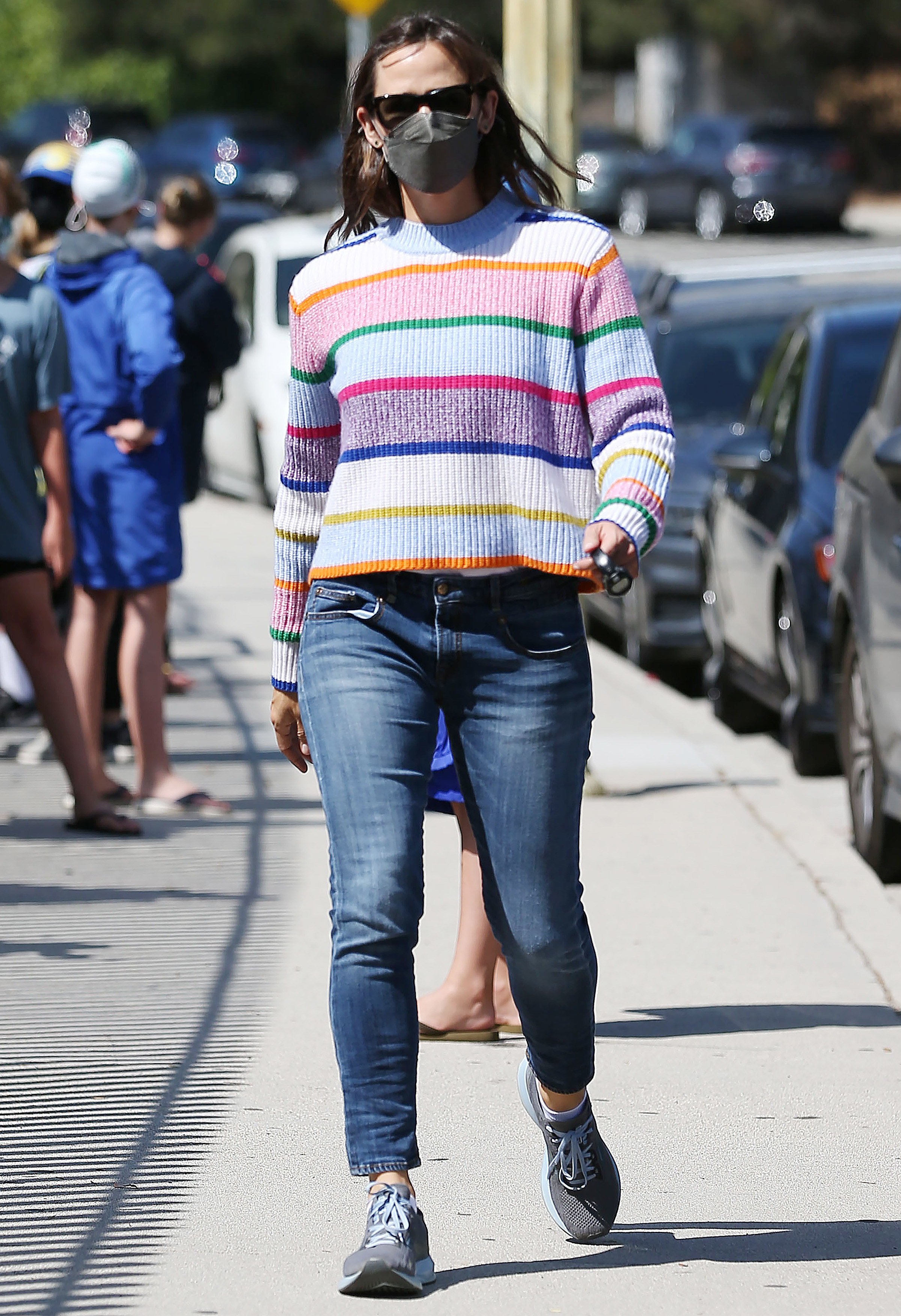Jennifer wears a striped mock turtleneck sweater with jeans and sneakers.