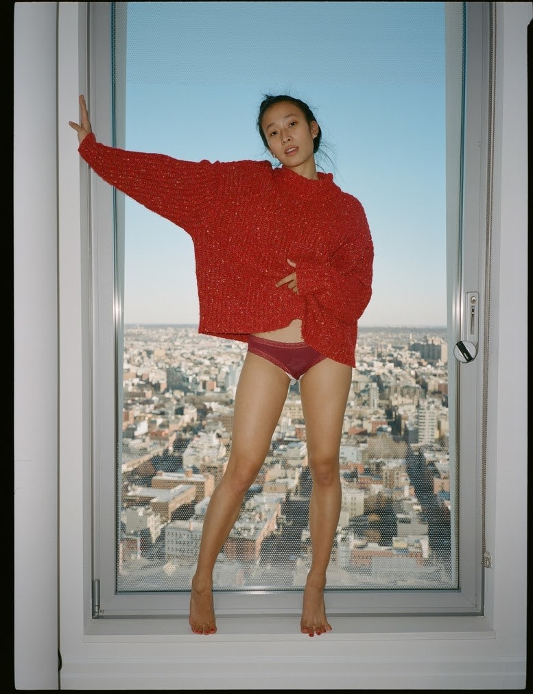 Nadya Okamoto standing in her underwear and sweater, visibly wearing a pad, in front of a window