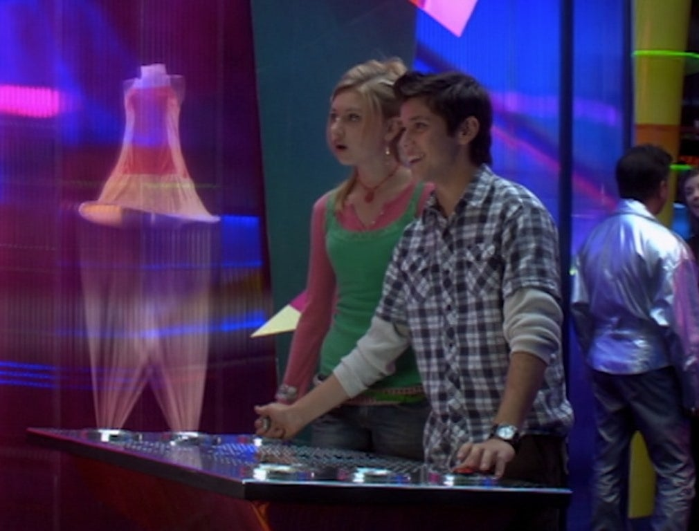 Aly Michalka and Ricky Ullman look at a hologram dress