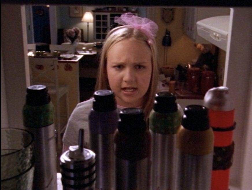 Amy Bruckner looks at a cabinet full of spray food