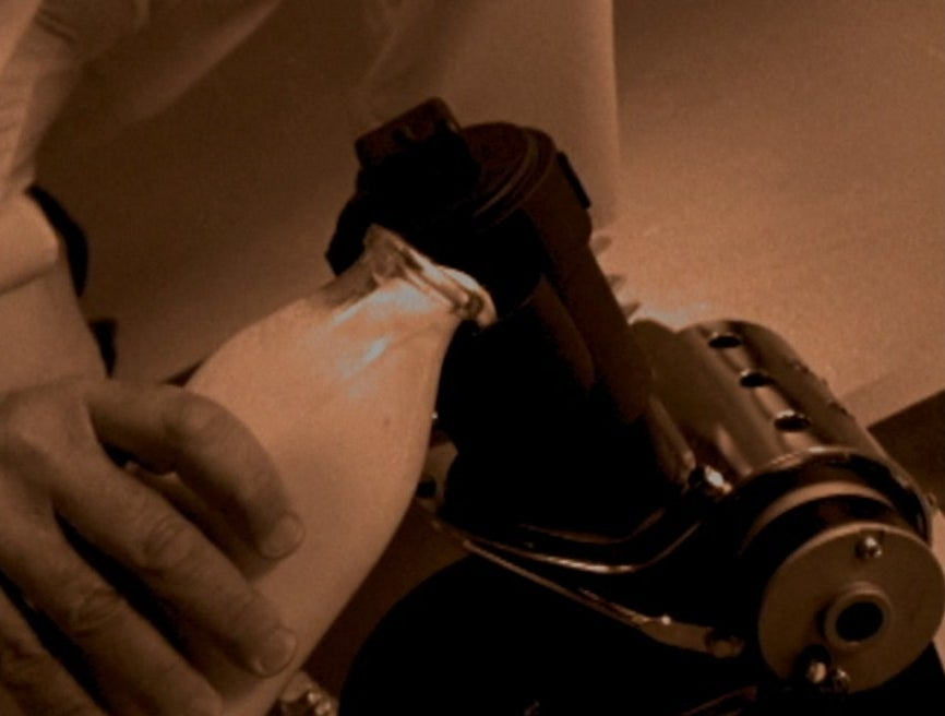 A hand pours milk into an engine