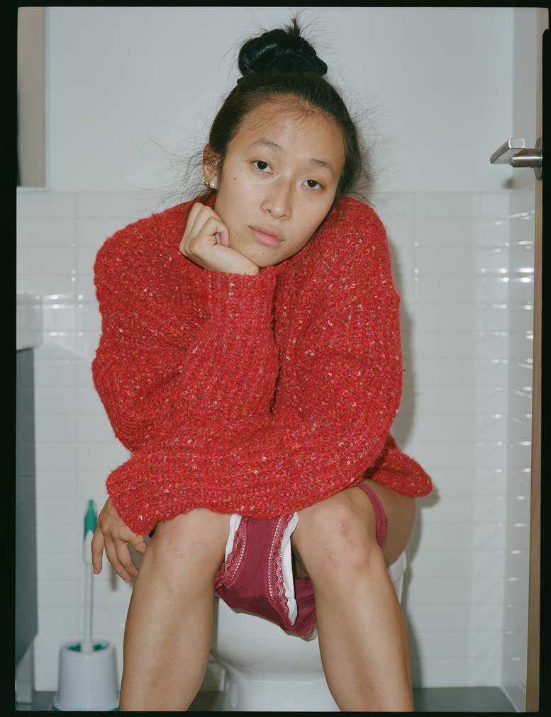 Nadya sits on a toilet with her underwear down, showing a pad