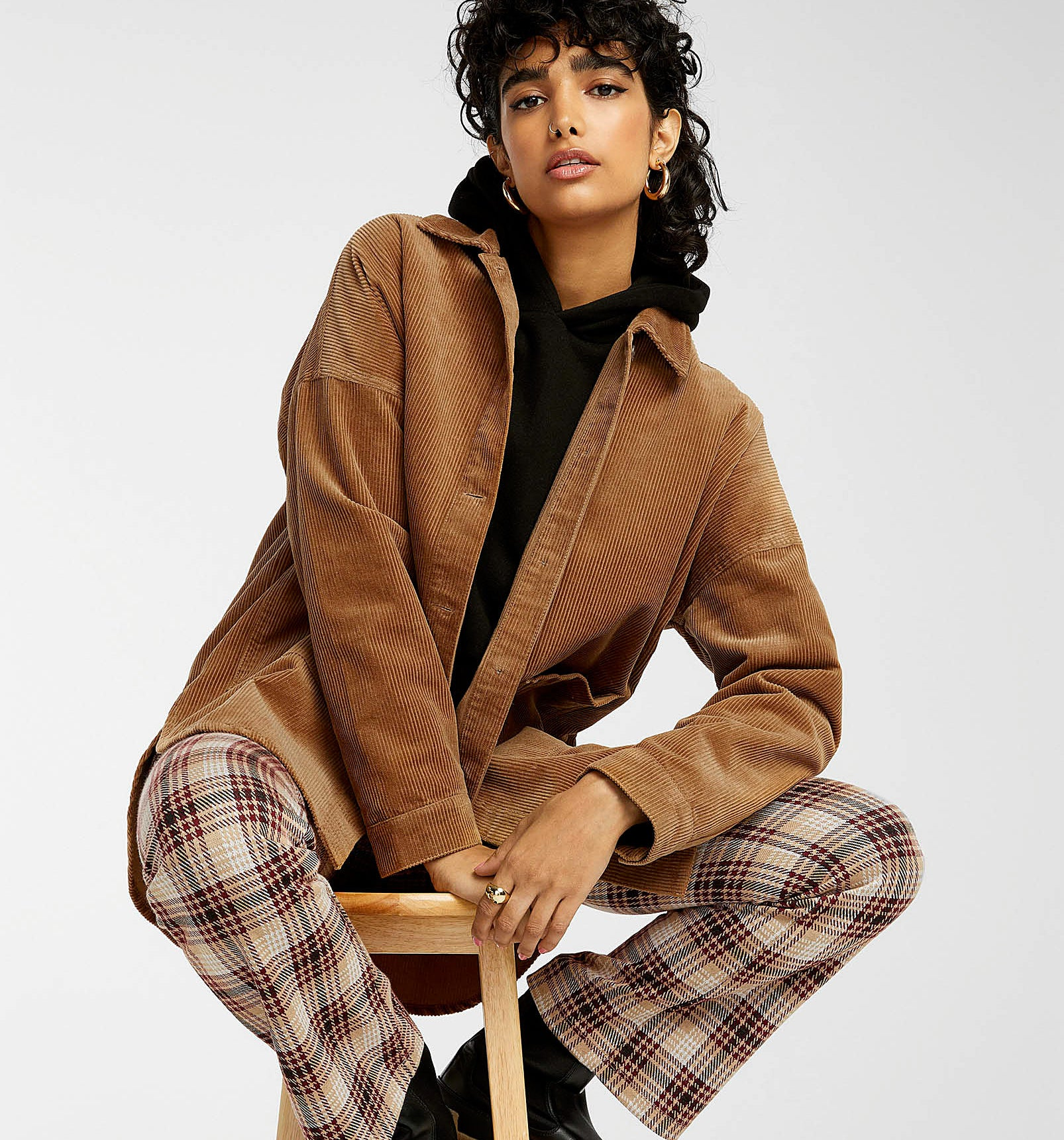 a person sitting on a stool wearing the corduroy jacket with checkered pants and rain boots