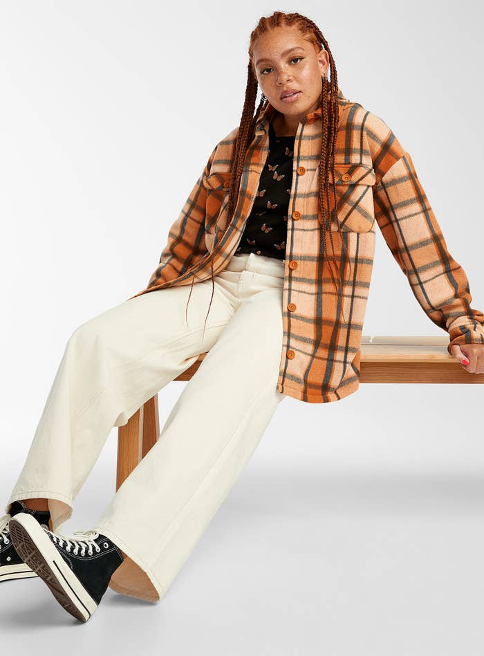 a person wearing the flannel shirt jacket with a t-shirt, white pants, and converse