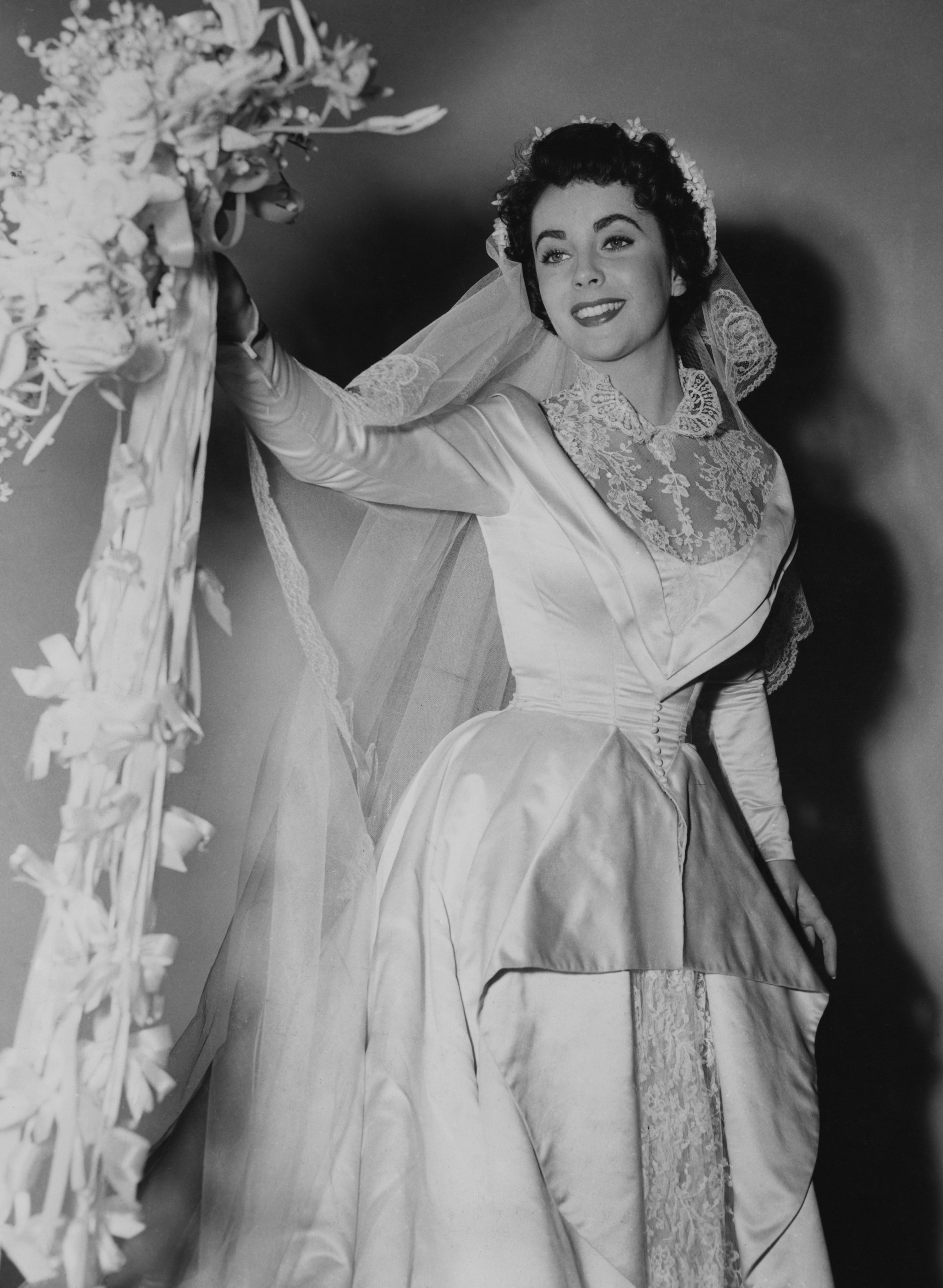 Kay wearing a huge, elaborate dress with a collar