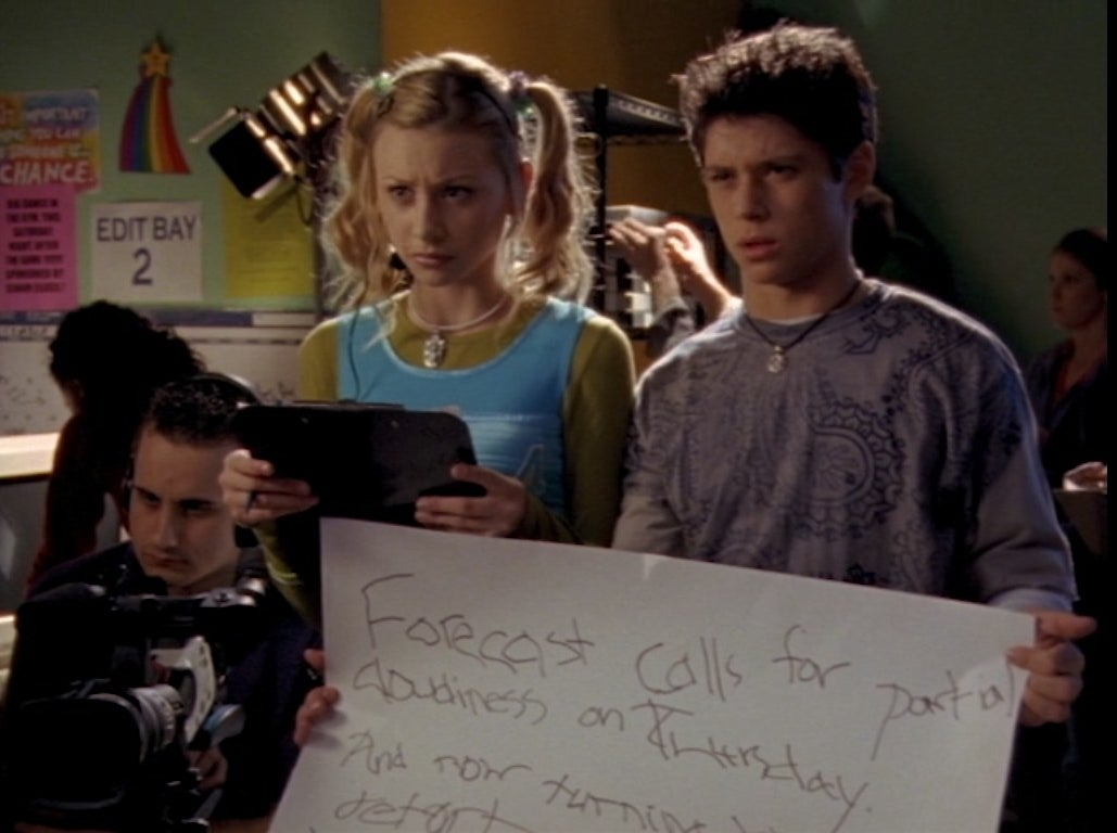Aly Michalka stands beside Ricky Ullman, who is holding a poorly written cue card
