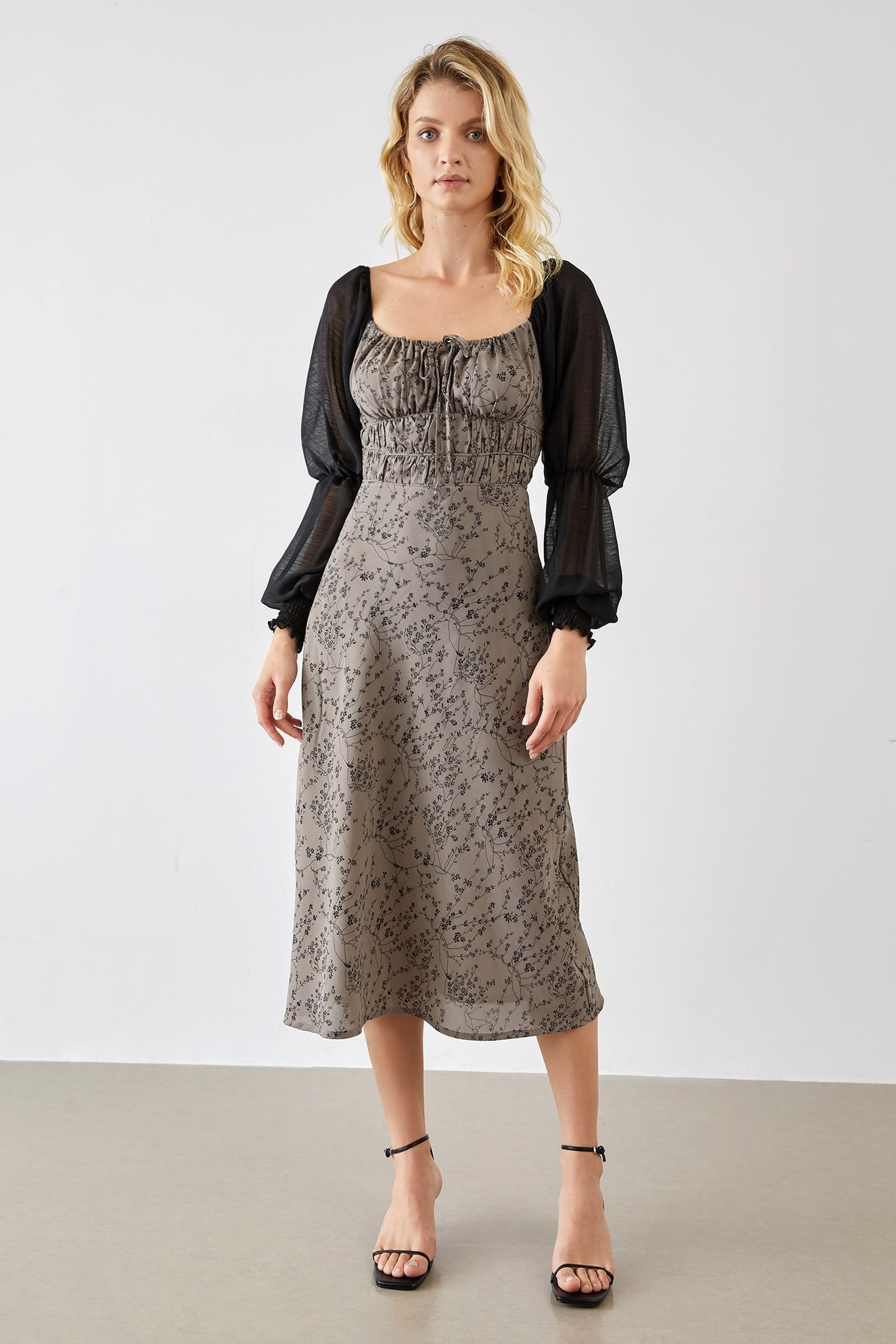 model wearing the mid-calf length grey dress with black floral patter and puffle black sleeves