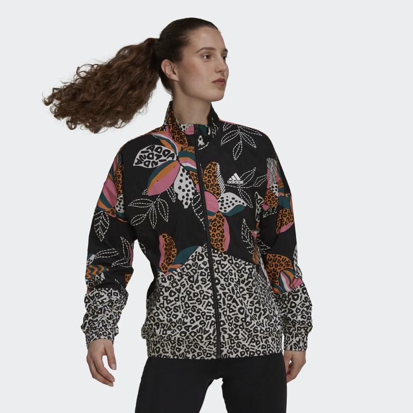 a person wearing a funky patterned adidas windbreaker