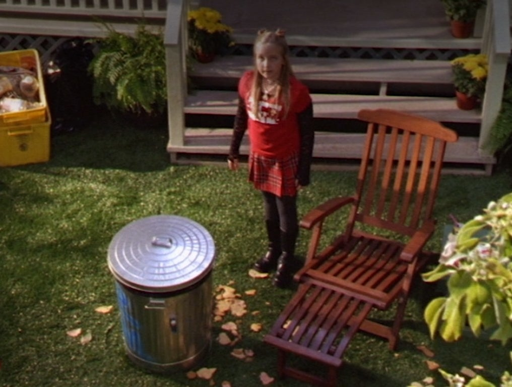 Amy Bruckner stands beside a garbage can with a penny missile on it