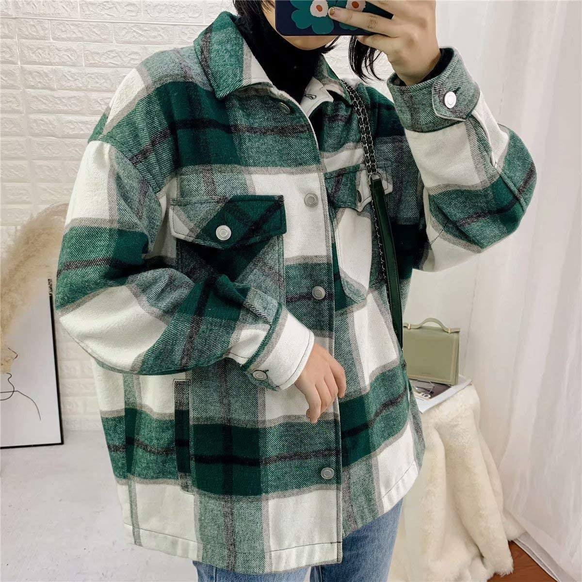 a person taking a photo of themselves in a mirror wearing the jacket