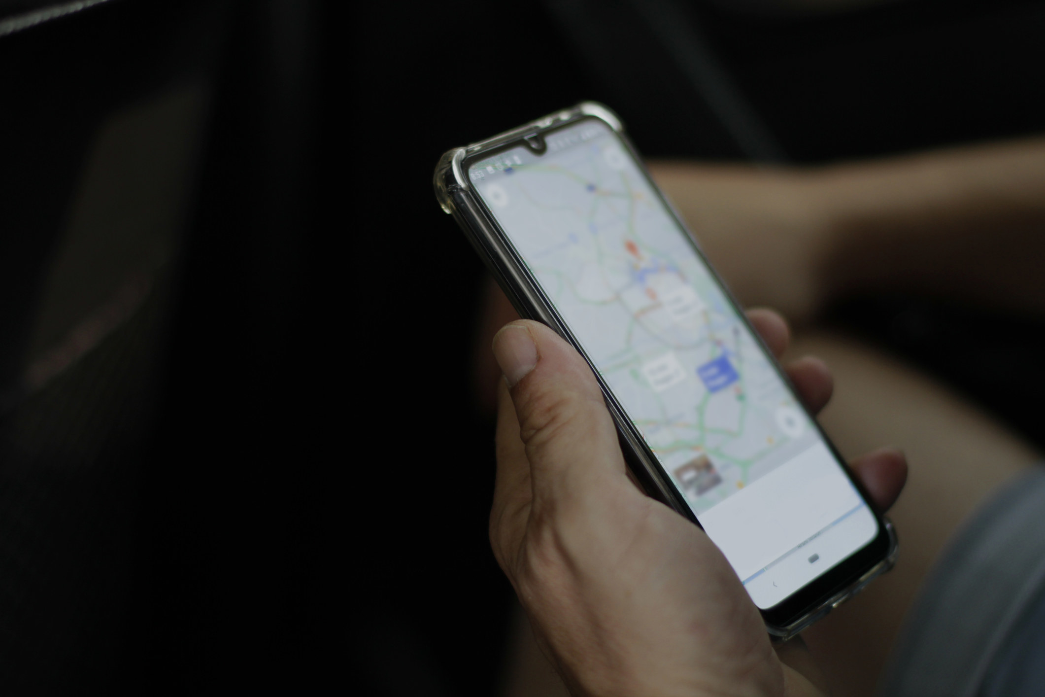 A hand holding a smartphone with a map on the screen.