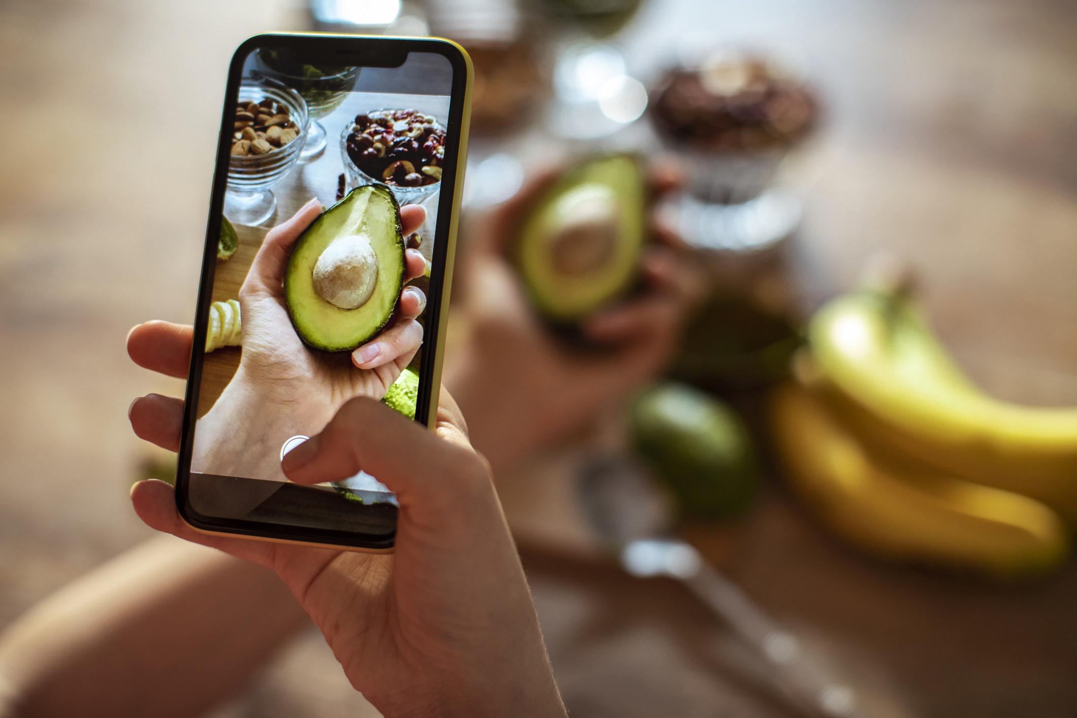 A person taking a photo of an avocado.