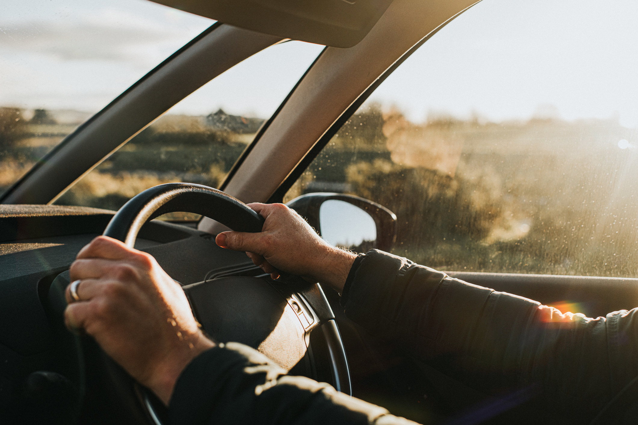 An up-close shot of a person holding a steering wheel driving a car.