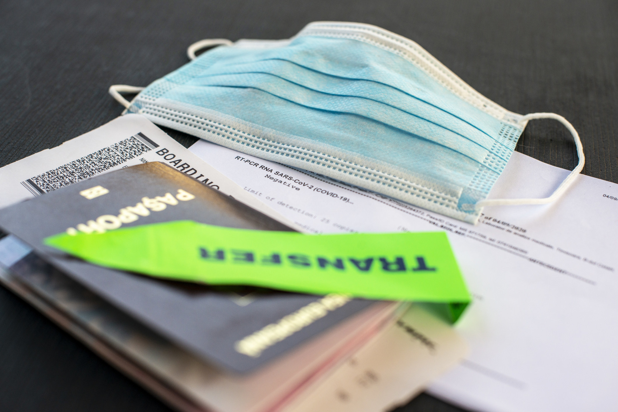 A passport, travel papers, and a face mask.