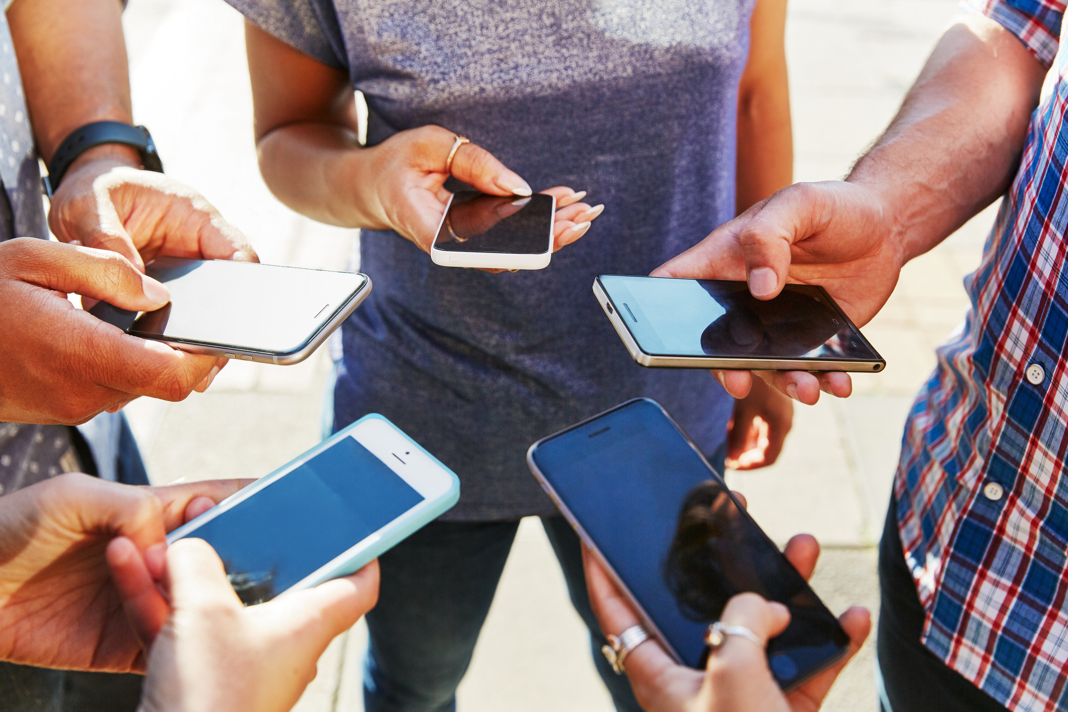 A group of hands holding smartphones in a circle.