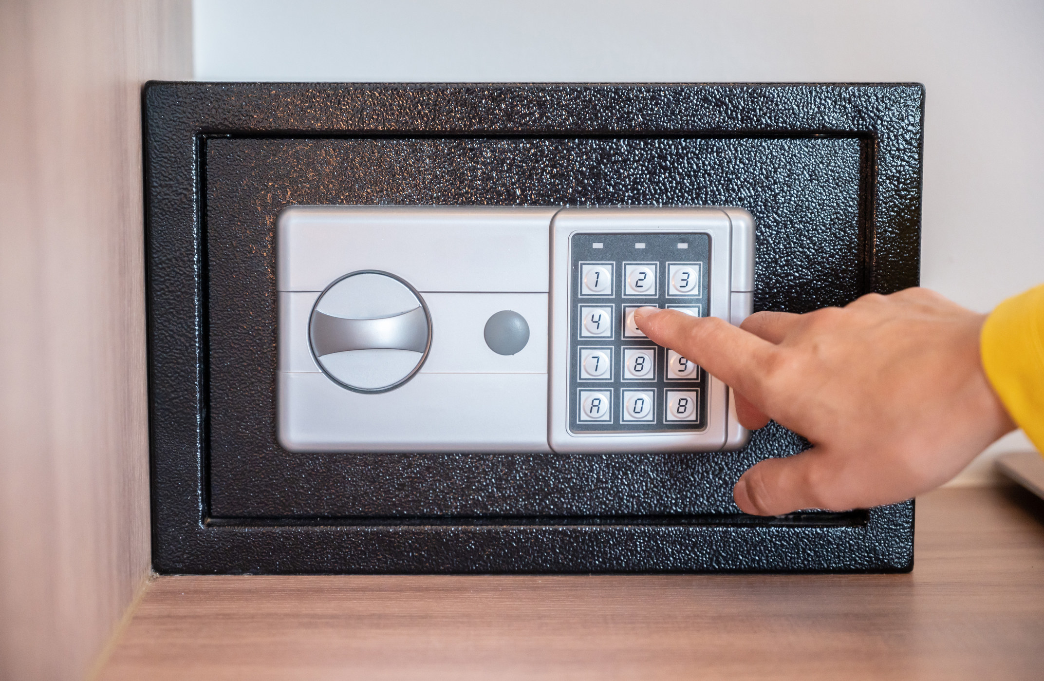 A hand entering a code into a hotel safe.