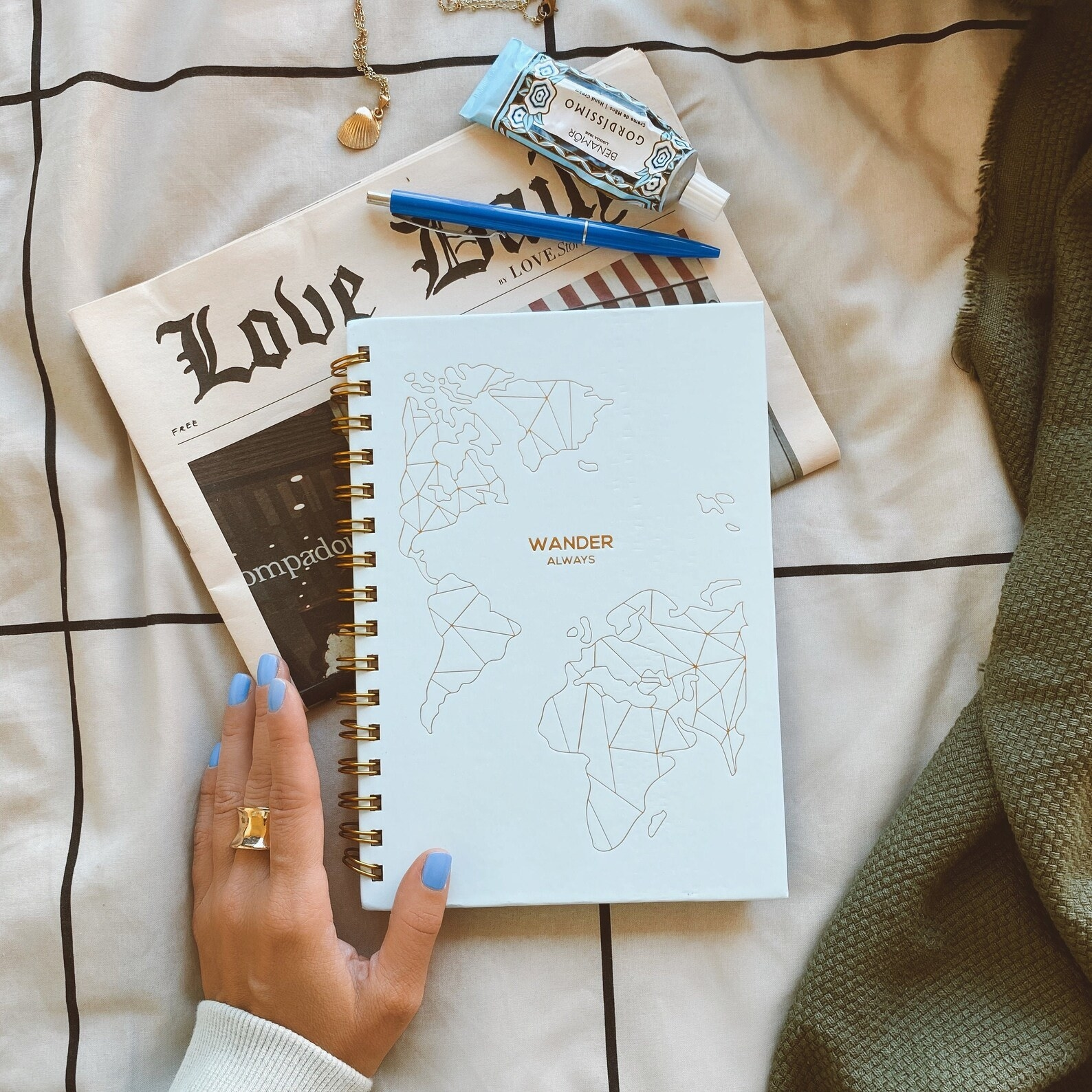 """Model holding spiral notebook with minimalist gold map that says """"Wander Always"""""""