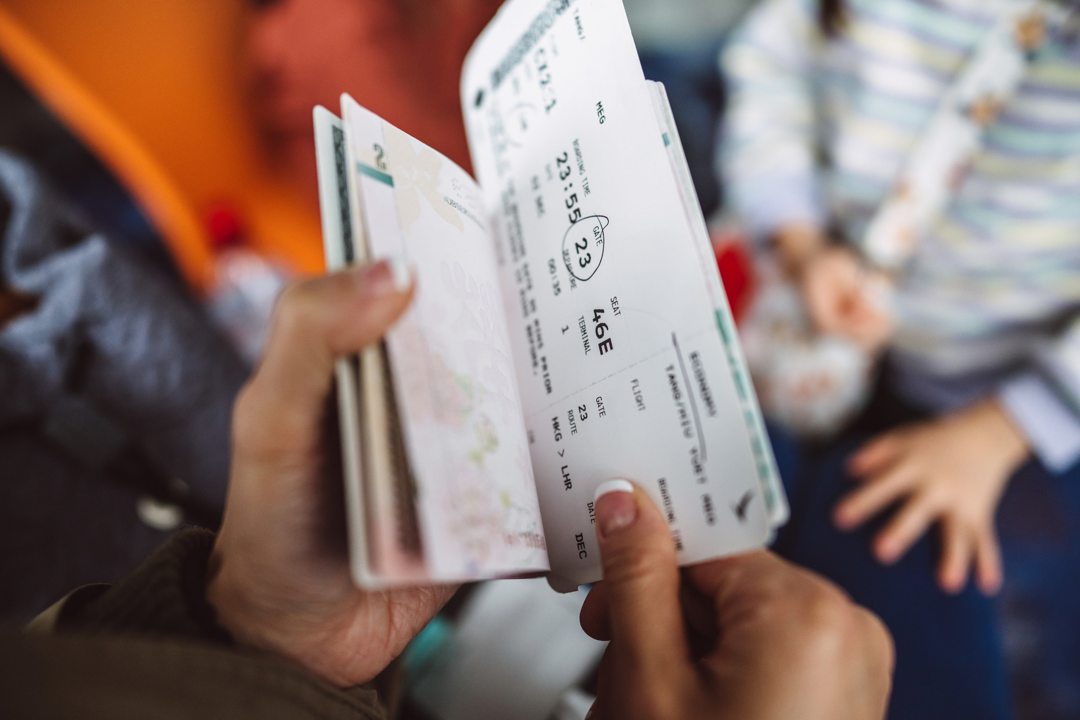 A hand holding travel documents.