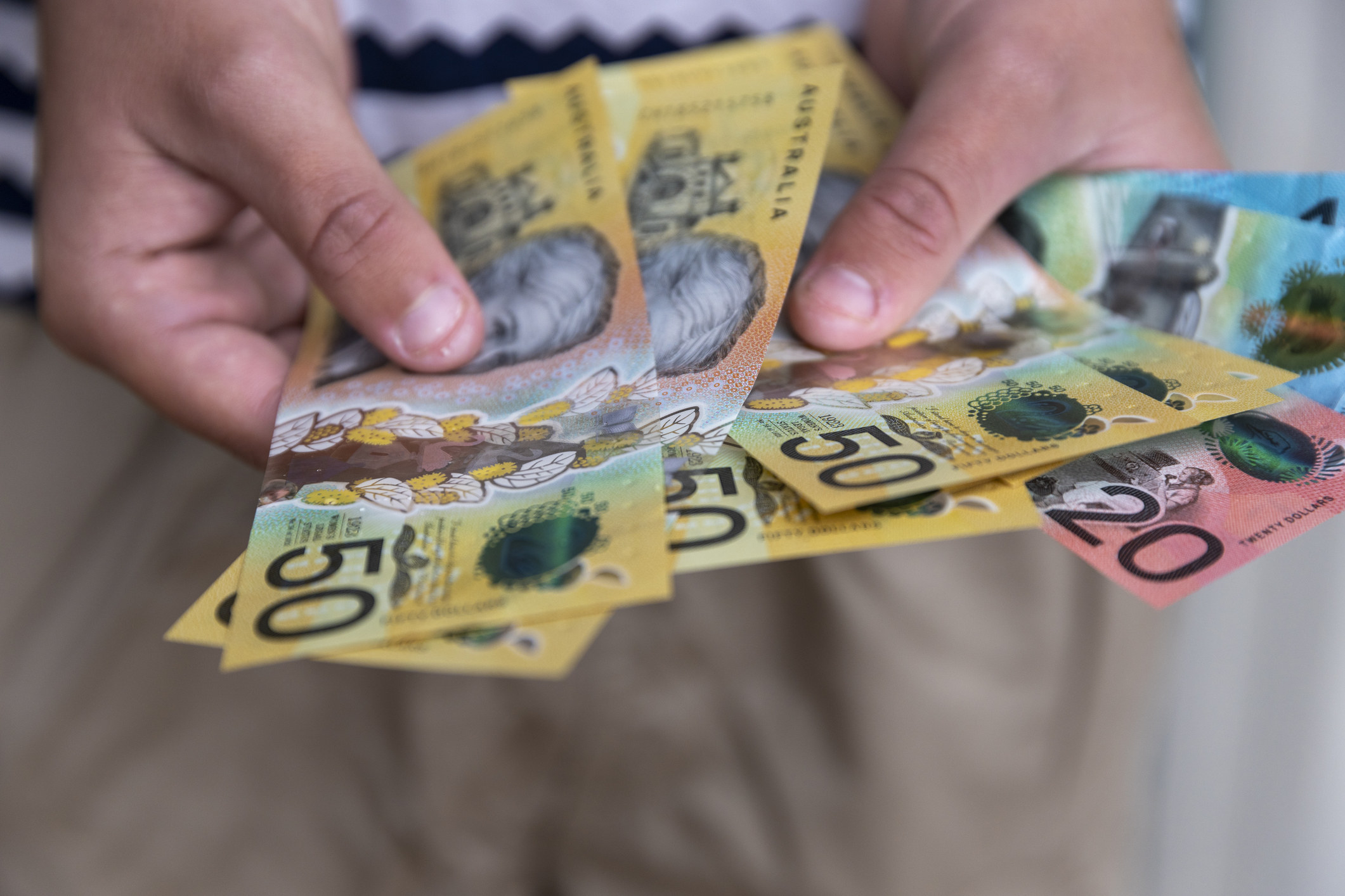 A hand holding Australian currency.