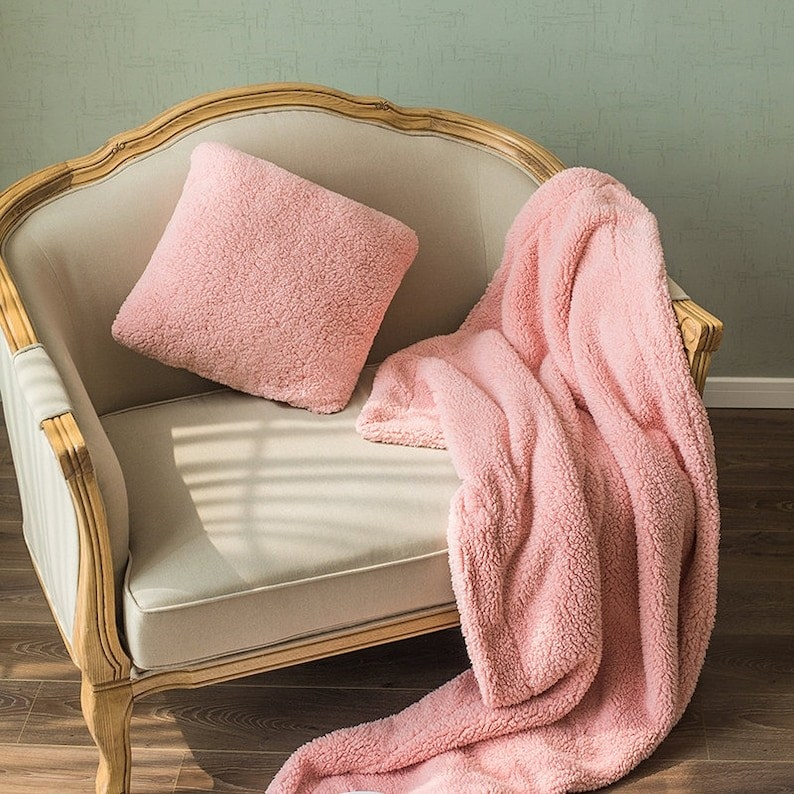A pink blanket and pink pillow on a chair