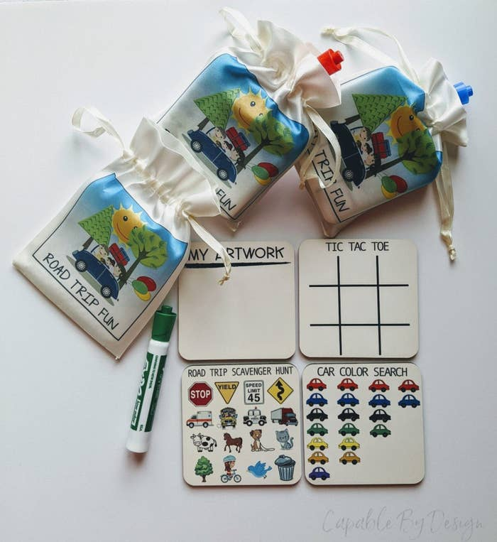 Four square boards with different games, a marker, and pouches