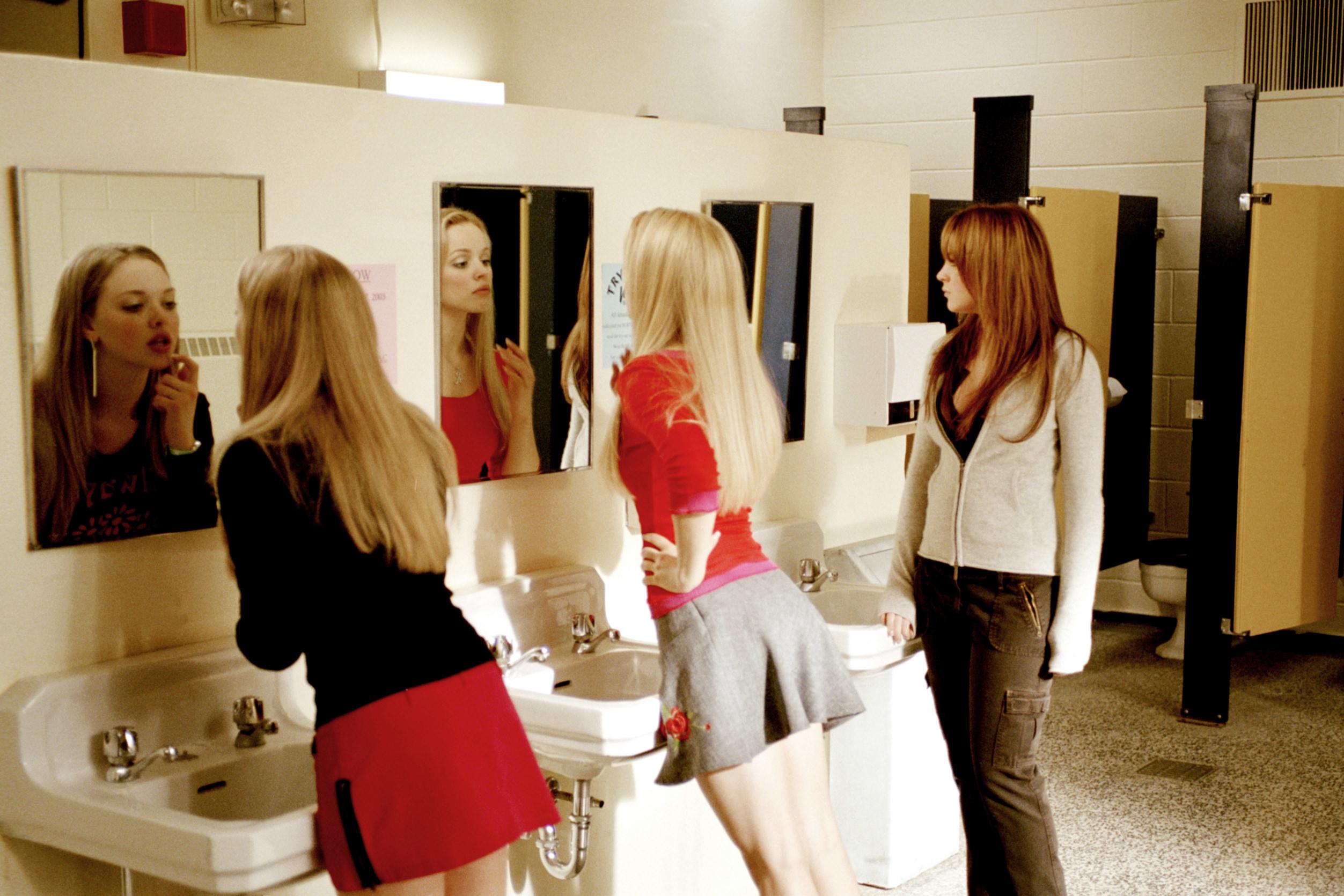 Karen and Regina fix their makeup in the bathroom mirrors