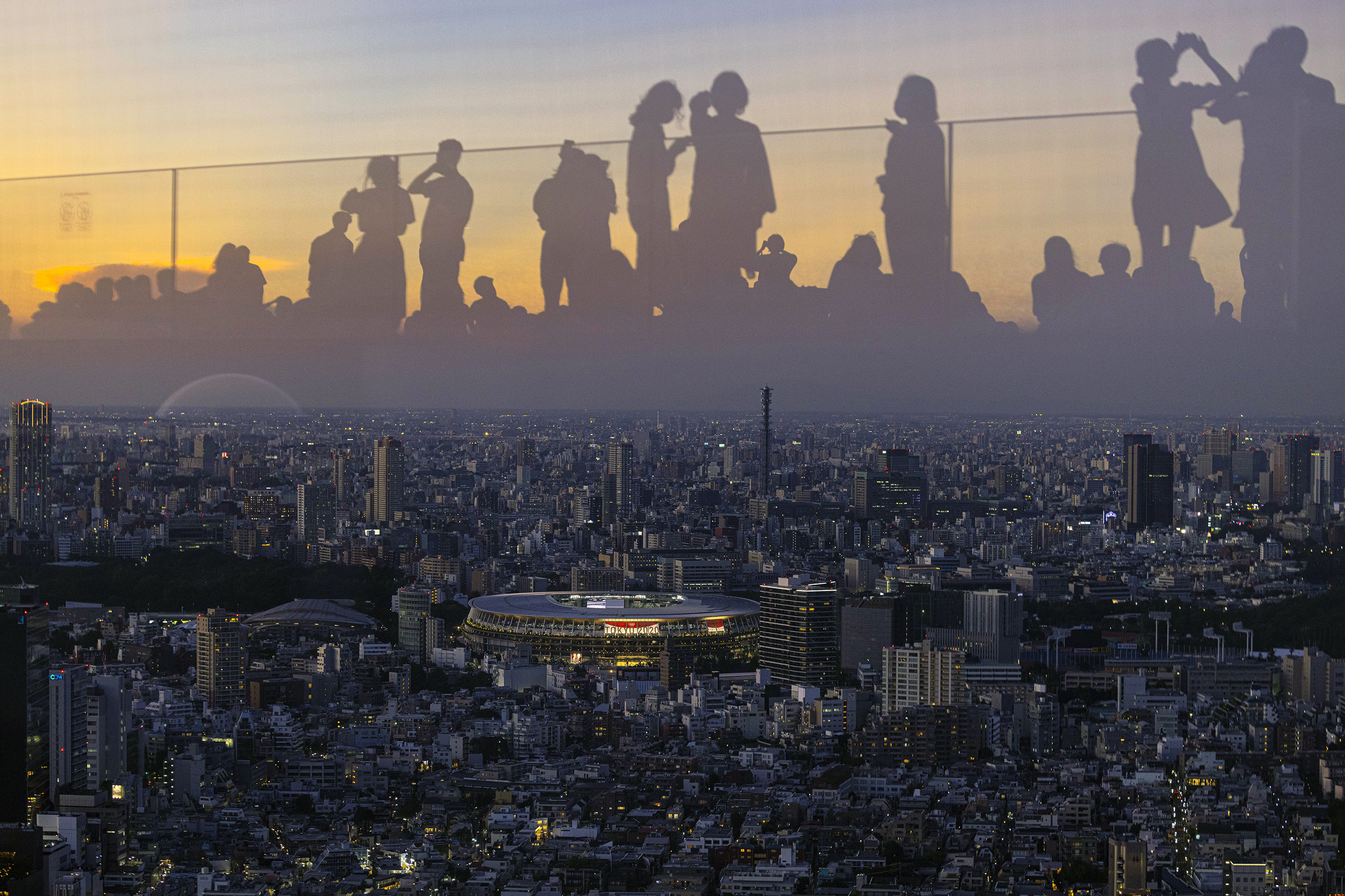 Tokyo's new National Stadium, as seen from the observation level of a nearby skyscraper with people reflected so that they appear on the skyline