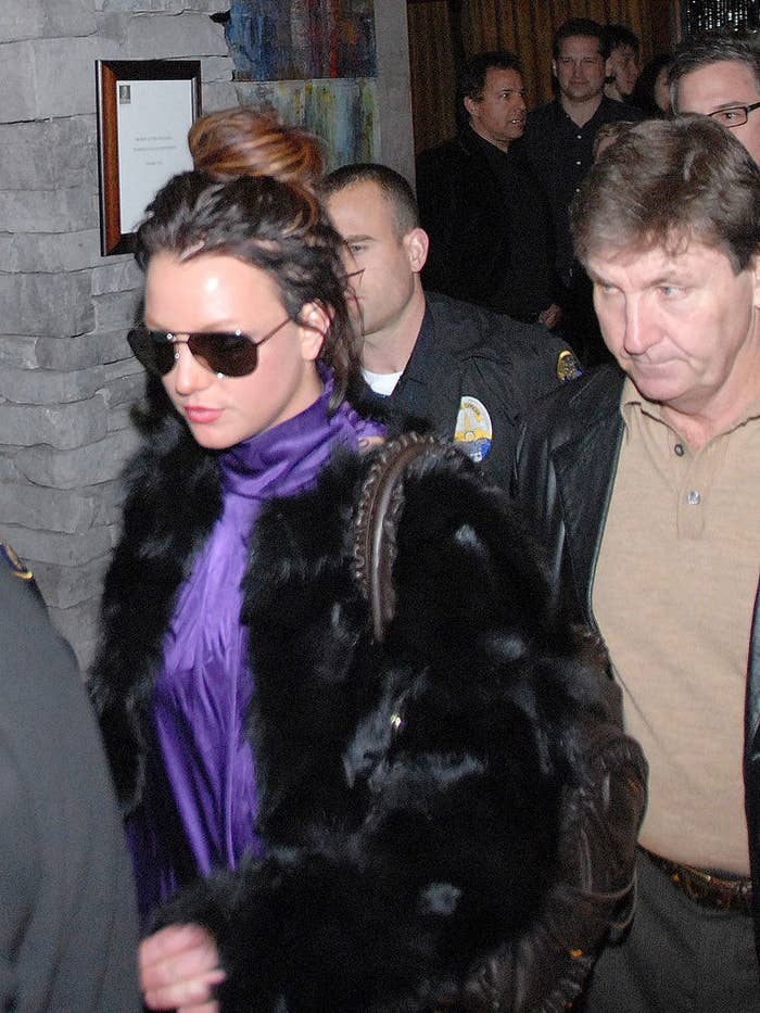 A young adult Britney, with dark hair, walking outside with her father behind her