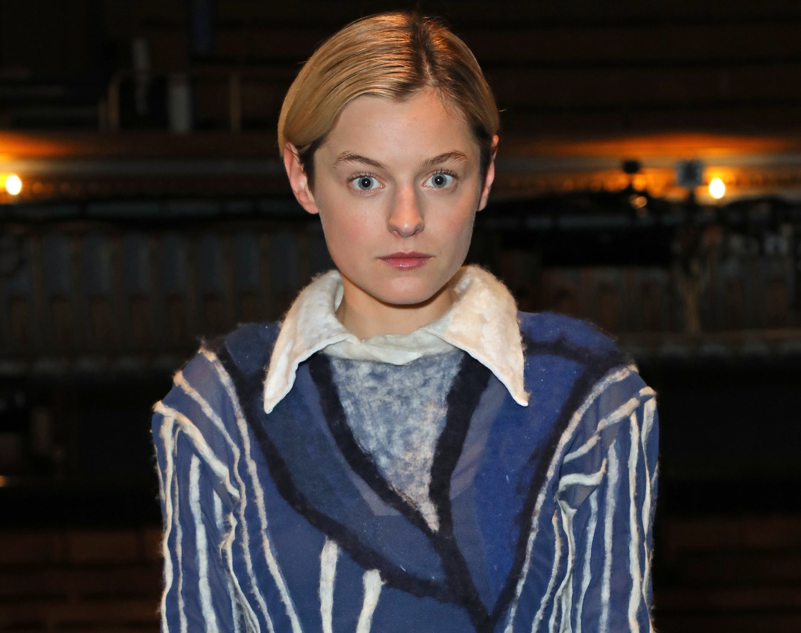 Emma wears a blue sweater with white stripes and collared shirt