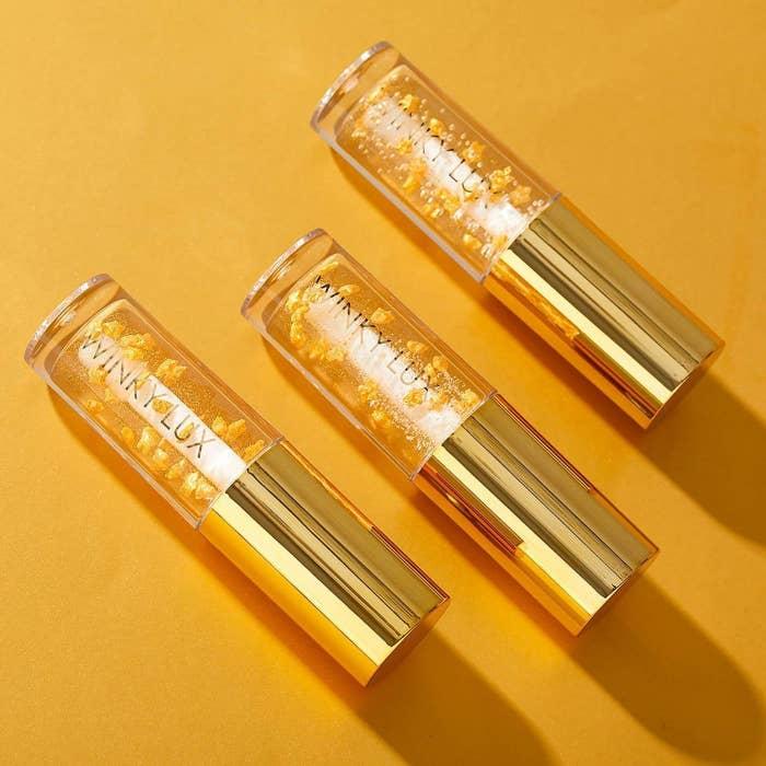 A row of three lip oils on a yellow backdrop