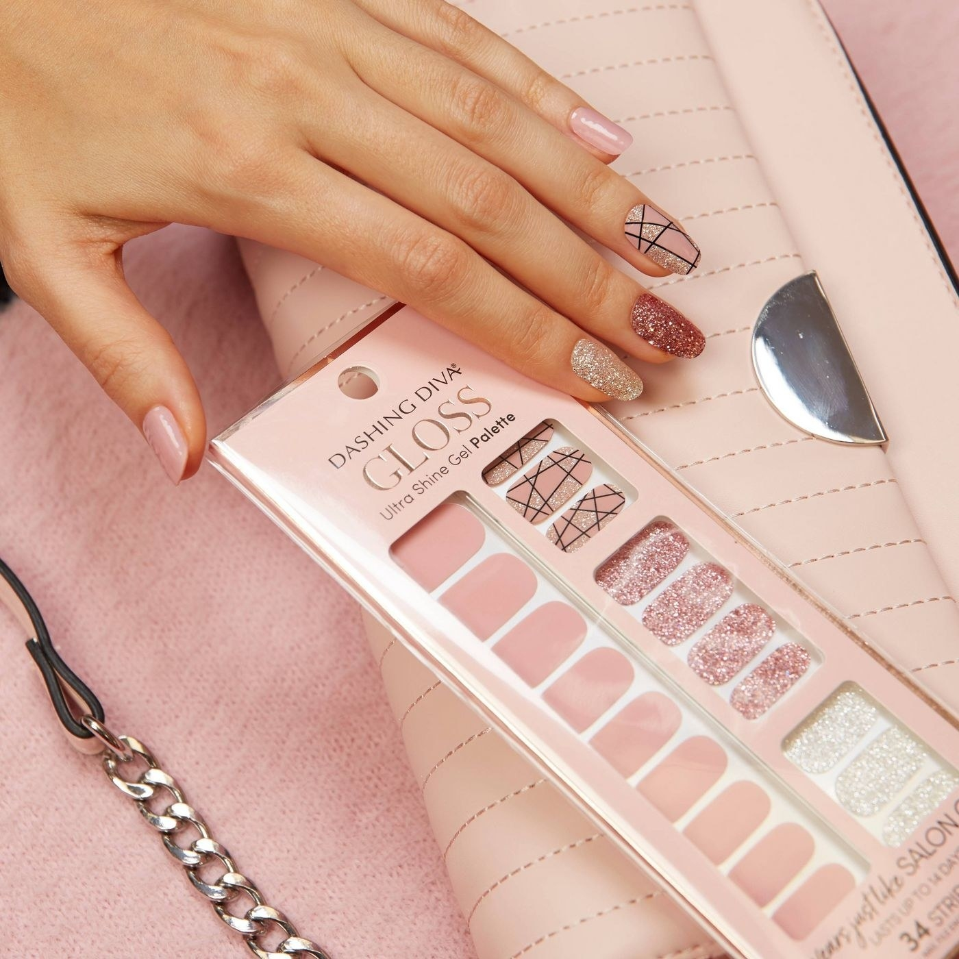 A hand reaching for a pack of light pink press on nails