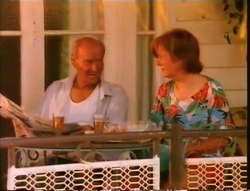 An older woman talks to her husband while sitting down on their balcony