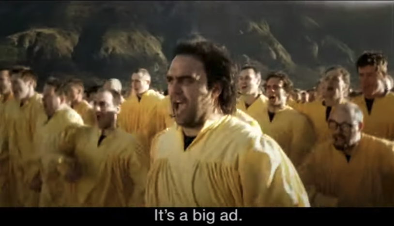 """An army of people dressed in yellow robes marching together; it is captioned """"It's a big ad"""""""