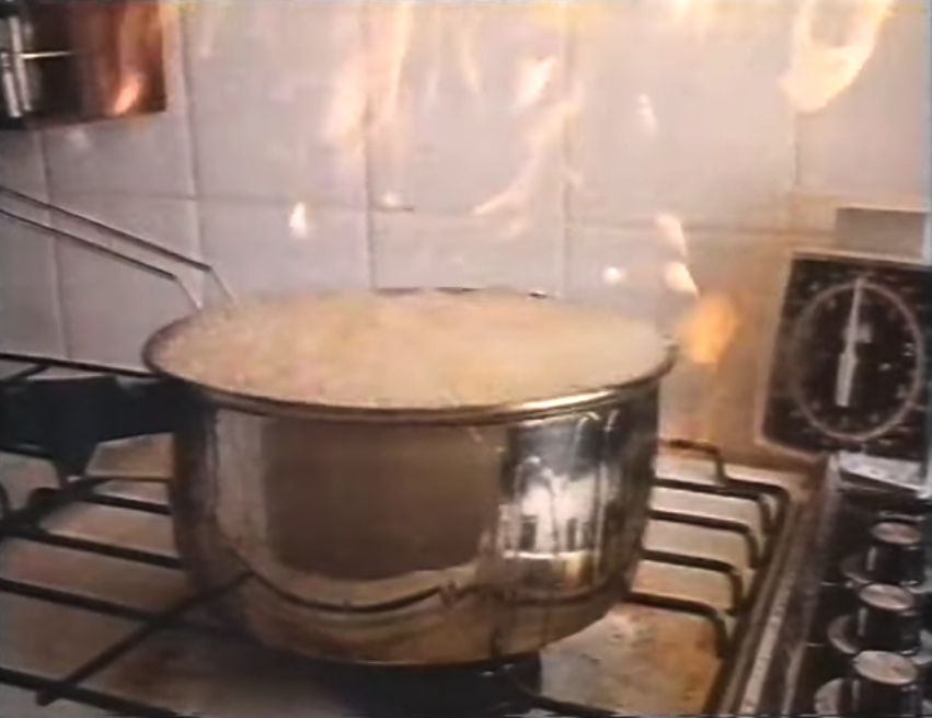 A pot filled with hot oil overfilling; the pot is on fire