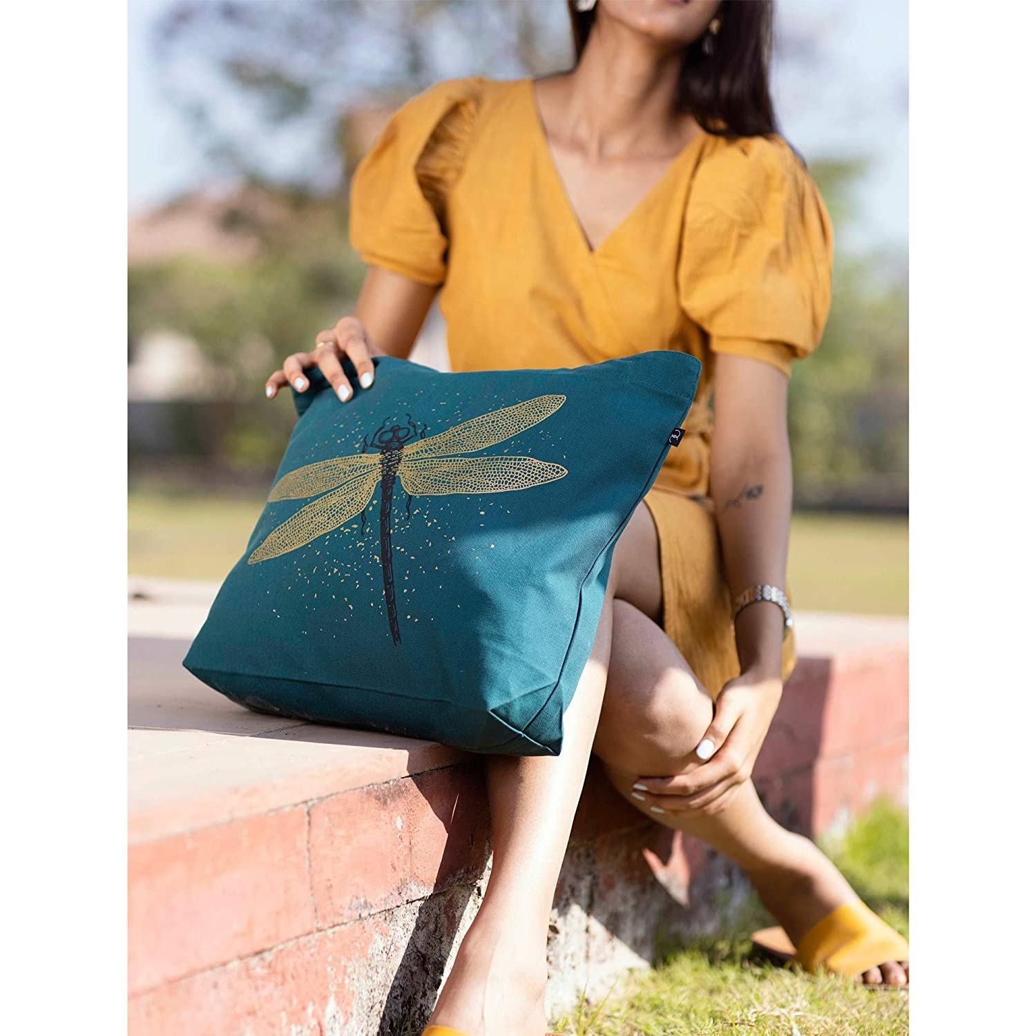 A teal tote bag with a golden dragonfly on it