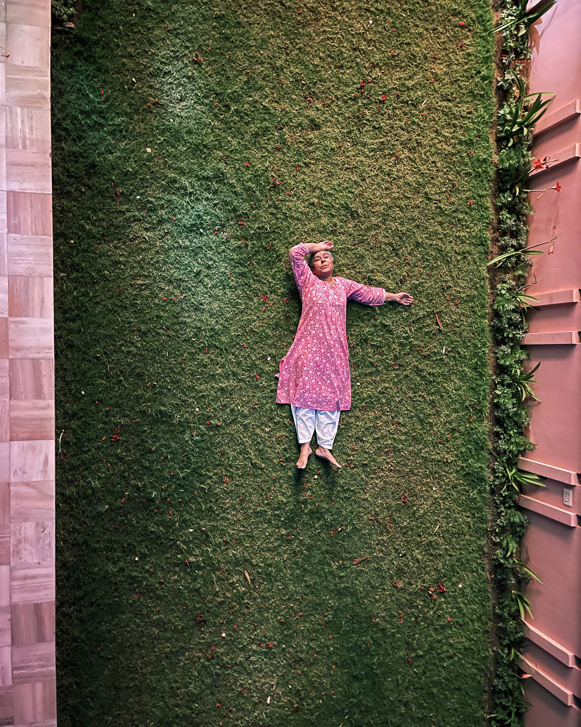 The photographer's mother lying down in the backyard, photographed from above